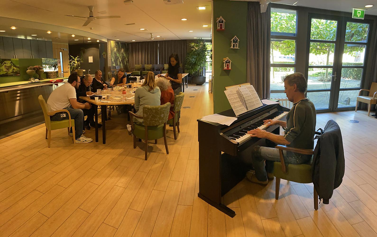 Revaliderende ouderen schilderen en tekenen op live pianomuziek